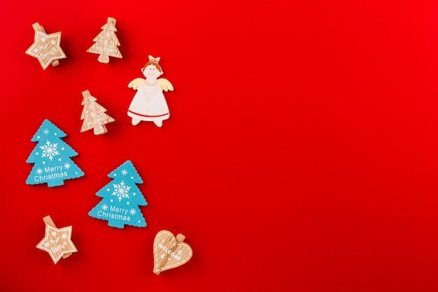 Kerst plat lag met houten figuren in de vorm van kerstbomen, engelen, sterren op een rood papier achtergrond met plaats voor tekst.
