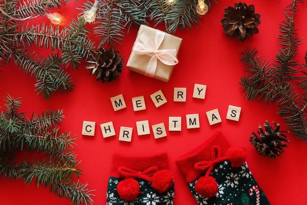 Kerst plat lag met kerstboomtakken, dennenappels, kerstsokken, cadeau en houten letters merry christmas op rood