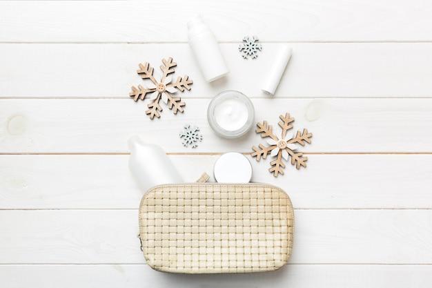 Kerst plat lag met make-up cosmetische producten in cosmetische zak op gekleurde achtergrond. bovenaanzicht nieuwjaar beauty concept.