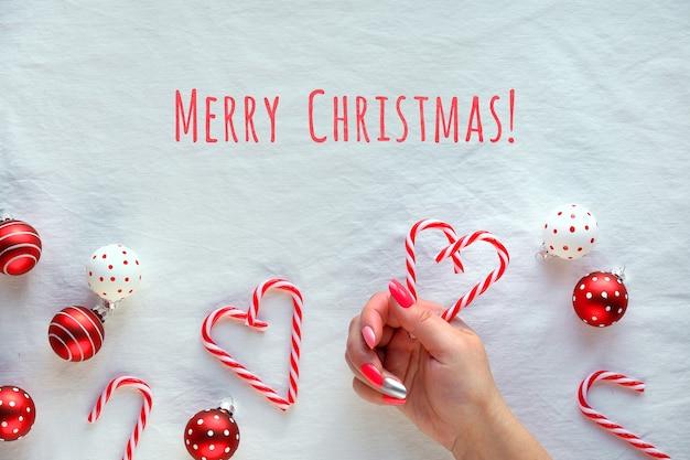 Kerst plat lag met rood wit gevlekte snuisterijen op wit textiel.