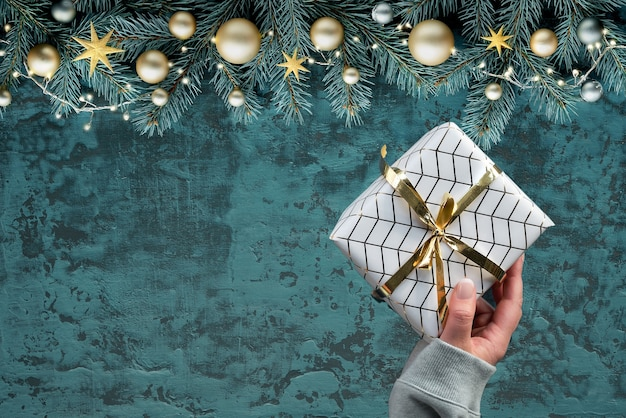 Kerst plat lag op donkergroen hout. hand met ingepakt cadeau