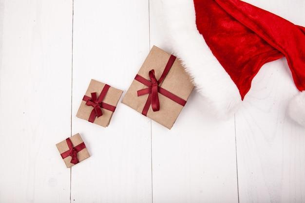 Kerst plat lag. presenteert en de hoed van de kerstman op wit houten