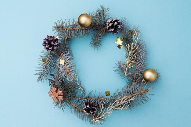 Kerst plat lag samenstelling in de vorm van een krans. takken van blauwe sparren, kegels, speelgoed op een blauwe achtergrond. kerstmis, winter, nieuwjaar concept. bovenaanzicht,.