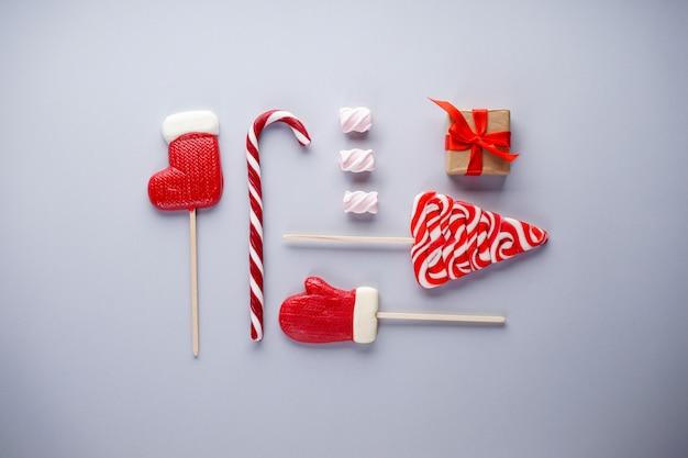 Kerst plat lag samenstelling. kerstmissuikergoed met marshmallows en een geschenk op grijs.