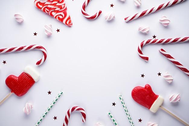 Kerst plat lag samenstelling. kerstmissuikergoed met marshmallows op grijs.