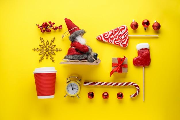 Kerst plat lag samenstelling. kerstsnoepjes, cadeau, speelgoed, kerstman in een slee, een wekker met een afkoeltijd en een kopje op geel.