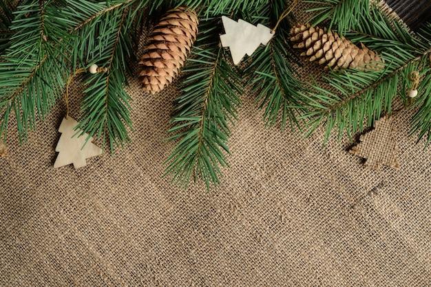 Kerst plat lag samenstelling met dennentakken op een jute achtergrond met kopie ruimte.