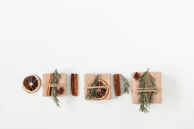 Kerst plat lag samenstelling van ambachtelijke geschenkdozen. handgemaakte bruine papieren doos met kerstboomtak en kaneelstokjes en droge sinaasappel. kopieer ruimte