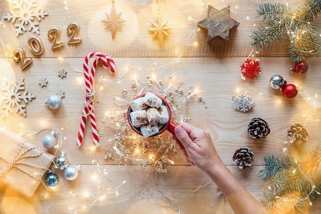 Kerst plat met een kopje marshmallow warme chocolademelk, zuurstokken, kerstverlichting en gouden 2022-nummers