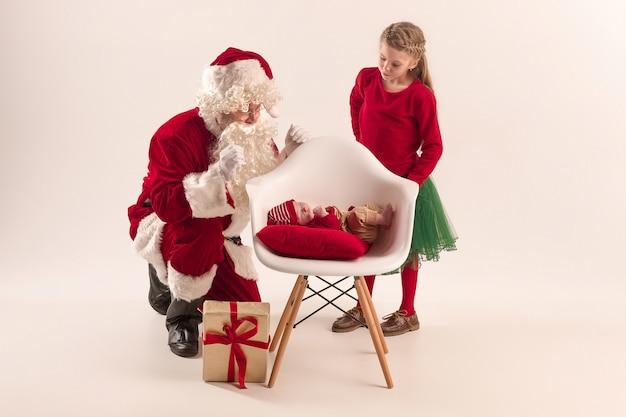 Kerst portret van schattig klein pasgeboren babymeisje en mooie tiener zus gekleed in kerst kleding en man met santa kostuum en hoed
