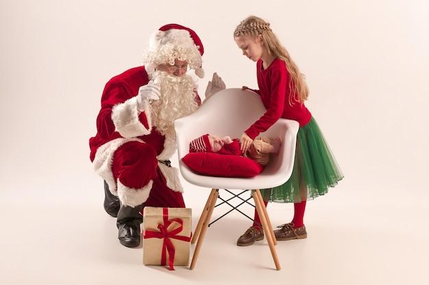 Kerst portret van schattig klein pasgeboren babymeisje, mooie tiener zus, gekleed in kerst kleding en kerstman met geschenkdoos