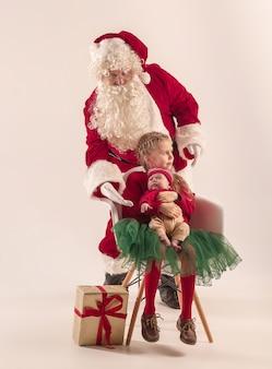 Kerst portret van schattig klein pasgeboren babymeisje, mooie tiener zus, gekleed in kerst kleding en man met santa kostuum en hoed, studio-opname, wintertijd. het concept van kerstmis, vakantie