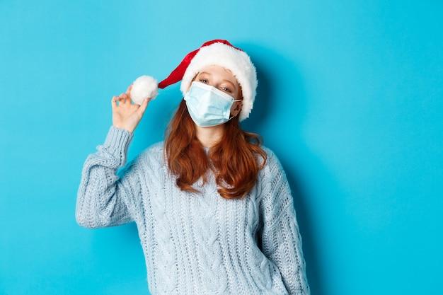 Kerst, quarantaine en covid-19 concept. vrolijk tiener roodharige meisje in kerstmuts en gezichtsmasker, staren camera tevreden, staande zelfverzekerd tegen blauwe achtergrond.