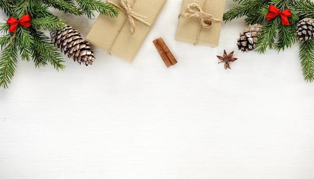Kerst rand samenstelling gemaakt van dennentakken, kegels geschenkdozen verpakt in kraftpapier op witte houten achtergrond. platliggend, bovenaanzicht, kopieerruimte