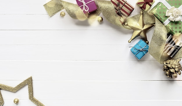Kerst rand samenstelling gemaakt van geschenkdozen gouden lint en kerstballen op witte houten tafel. plat leggen, ruimte kopiëren. retro stijl afgezwakt