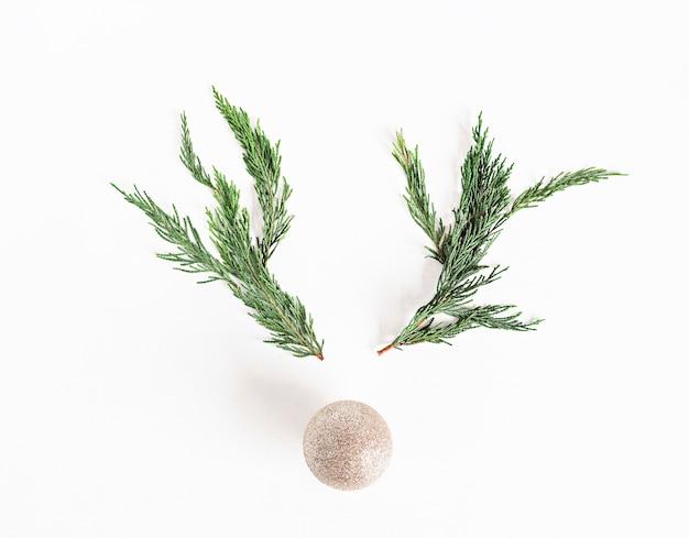 Kerst rendieren concept gemaakt van takken en kerstbal. minimalistisch winter seizoensgebonden idee. plat lag, bovenaanzicht samenstelling