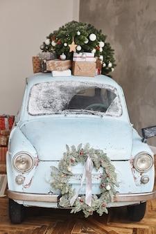 Kerst retro auto versierd geladen met kerstboom en cadeautjes
