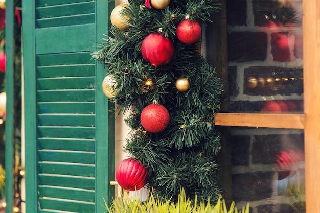 Kerst rode bal versierde ramen op vintage huis.