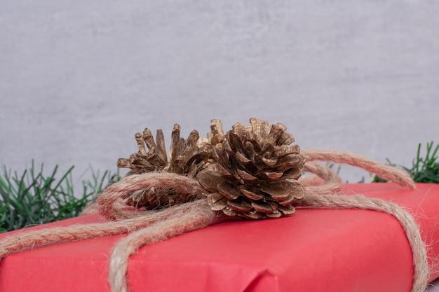 Kerst rode doos met pinecone op grijs.