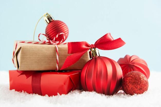 Kerst rode en ambachtelijke geschenkdozen met rode kerstballen op sneeuw.