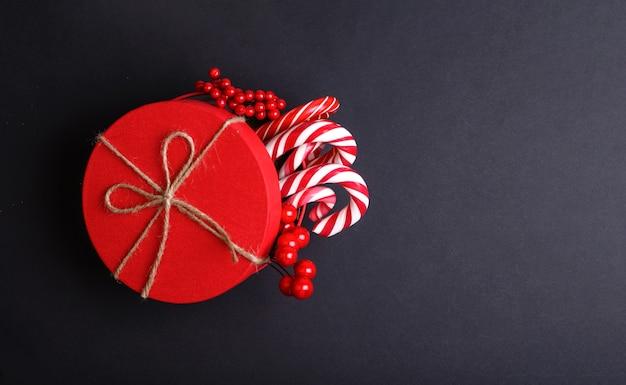 Kerst rode geschenkdoos decoratie met candy canes op zwarte achtergrond