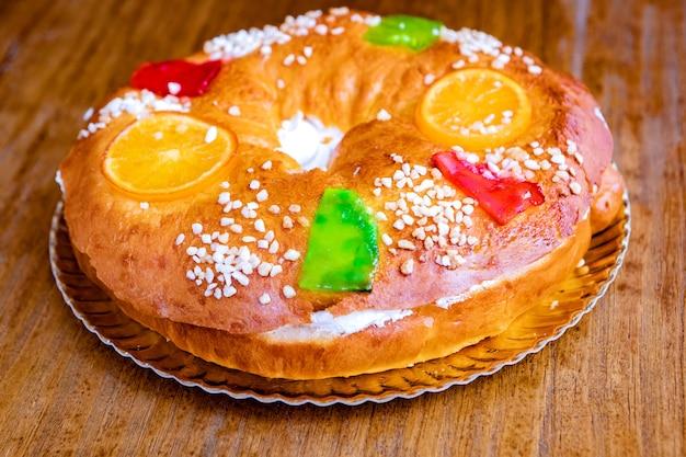 Kerst ronde fruitcake versierd met sparrentak, geglazuurde vruchten en noten op een houten tafel.