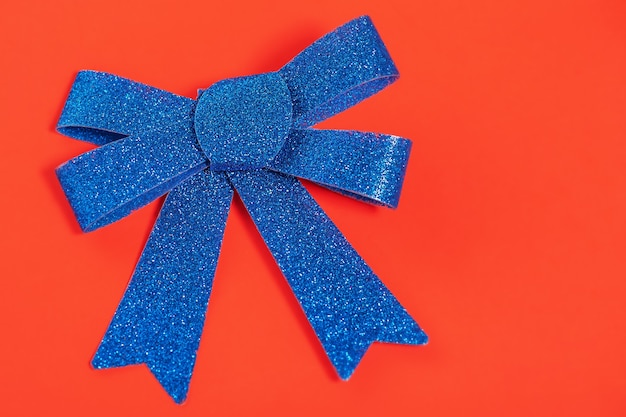 Kerst samenstelling blauwe glitter strik op een rode achtergrond. kerstkaart, kopieer ruimte.