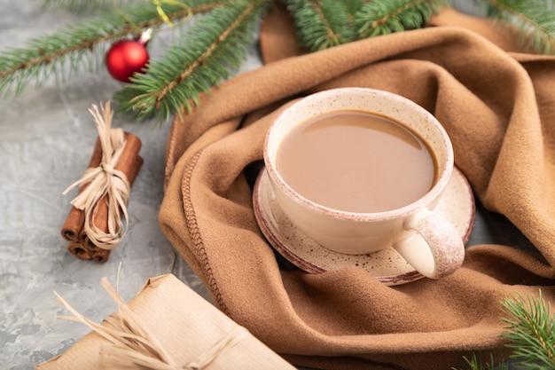Kerst samenstelling. decoraties, doos, kaneel, sparren en sparren takken, kopje koffie, wollen sjaal op grijs beton.