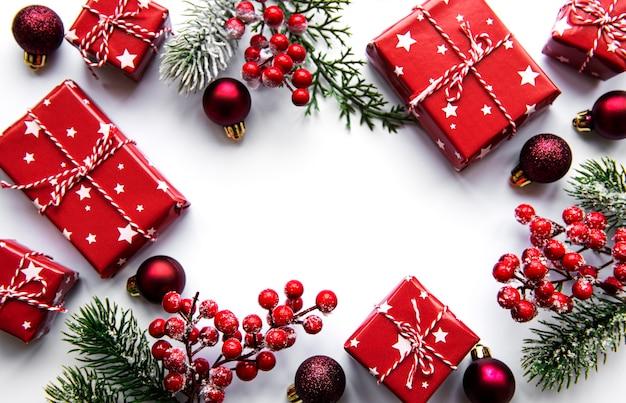 Kerst samenstelling. fir tree takken, rode decoraties op wit