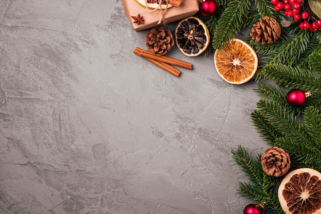 Kerst samenstelling. geschenkdoos, ballen, kaneel, anijs, gedroogd fruit, dennenappels en dennennaalden decoraties op grijze achtergrond. bovenaanzicht kopie ruimte