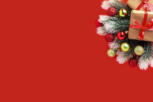 Kerst samenstelling. geschenkdoos, dennentakken, rode gouden ballen op rood, nieuwjaarsconcept. plat leggen, bovenaanzicht, kopie ruimte