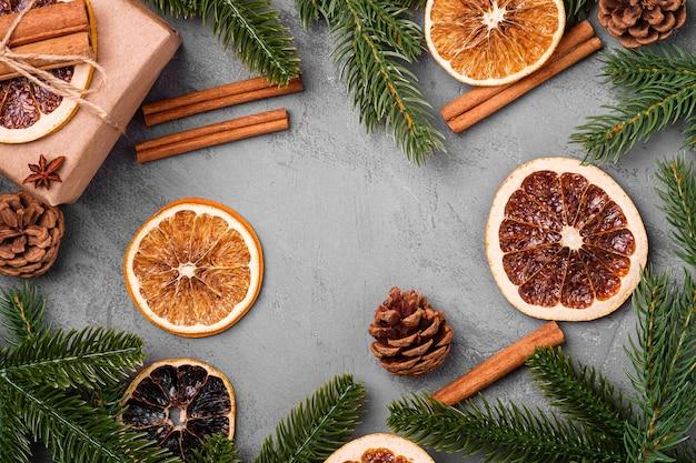 Kerst samenstelling. geschenkdoos, kaneel, anijs, gedroogd fruit, dennenappels en dennennaalden decoraties op grijze achtergrond. bovenaanzicht kopie ruimte