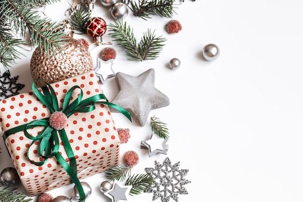 Kerst samenstelling. geschenken, fir tree takken, rode versieringen op witte muur. winter, nieuwjaarsconcept. plat leggen, isometrisch, ruimte voor tekst