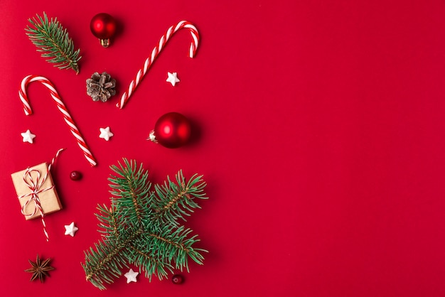 Kerst samenstelling. geschenken, fir tree takken, snoep, decoraties op rode achtergrond. plat leggen