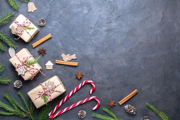Kerst samenstelling. kerstcadeau, decoraties, dennenappels, dennentakken op zwart. plat leggen