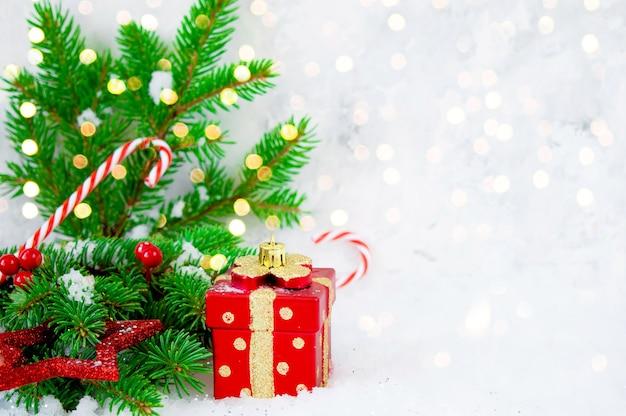 Kerst samenstelling. kerstcadeau, fir takken, sneeuw op houten witte achtergrond. plat lag, bovenaanzicht. kopieer ruimte. concept voor nieuwjaar, wintervakantie.