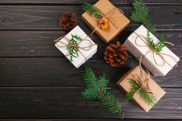 Kerst samenstelling. kerstcadeau, gebreide deken, dennenappels, dennentakken op houten.