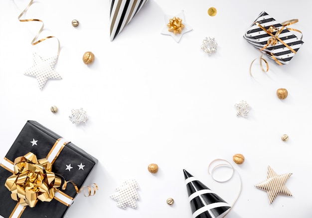 Kerst samenstelling. kerstcadeaus, feestmutsen, zwarte en gouden decoraties op witte achtergrond. plat leggen, kopie ruimte