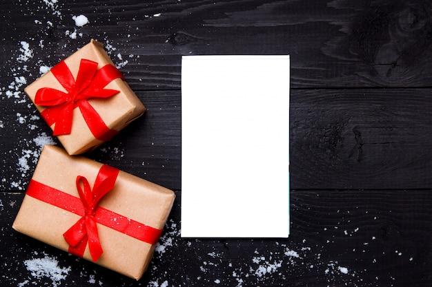 Kerst samenstelling. kerstmisgiften en blocnote op houten zwarte achtergrond. bovenaanzicht, plat lag, kopie ruimte.
