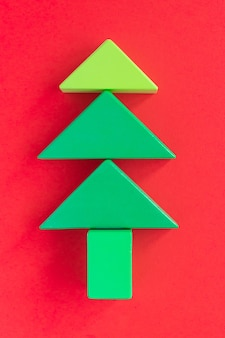 Kerst samenstelling kinderen. kerstboom gemaakt van groene houten constructie blokken tegen rode achtergrond. kleurrijk educatief speelgoed voor kinderen. bovenaanzicht. plat leggen.