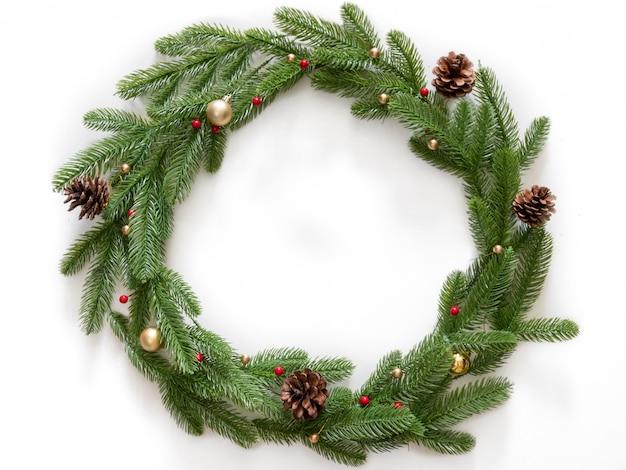 Kerst samenstelling. krans gemaakt van kerstboom takken en dennenappels met gouden bubbels op witte achtergrond