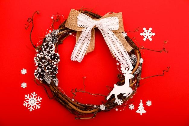 Kerst samenstelling. met de hand gemaakte kroon op rode achtergrond. plat lag, bovenaanzicht, kopie ruimte, vierkant. komst- of kerstkrans