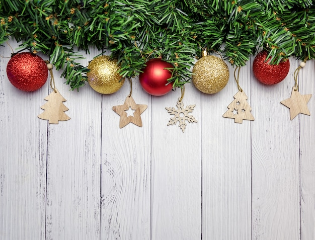 Kerst samenstelling met fir takken, gouden en rode ballonnen, houten speelgoed op een witte houten achtergrond.