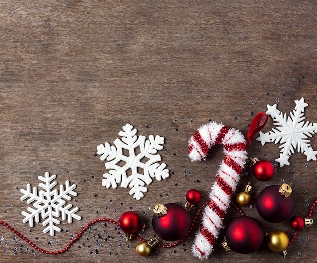 Kerst samenstelling met kerstballen, sneeuwvlokken en snoep boom speelgoed op houten achtergrond. kerstmis, nieuwjaar concept. plat lag, bovenaanzicht, kopie ruimte
