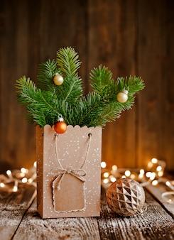 Kerst samenstelling. papieren zak met en stoten fir takken op bruine houten achtergrond en bokeh lichten.