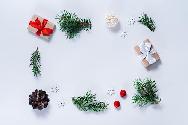 Kerst samenstelling. rand van pijnboomtakken met decoraties voor de feestdagen op witte achtergrond. bovenaanzicht, plat gelegd.