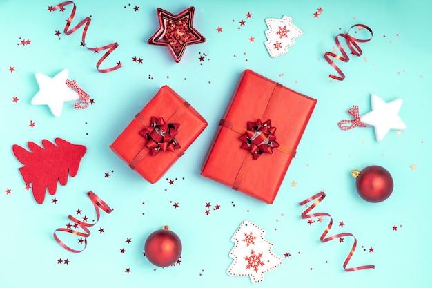 Kerst samenstelling. rode en witte kerstversiering op pastel blauw papier achtergrond.