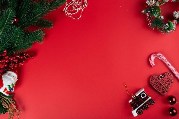 Kerst samenstelling. rode kerstversiering, kerstboomtakken op rode achtergrond. plat leggen, bovenaanzicht, kopie ruimte.