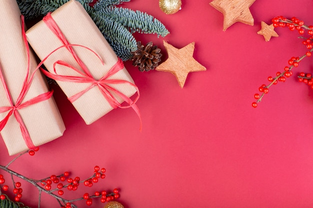 Kerst samenstelling. rode kerstversiering, spar takken met speelgoed geschenkdozen op rode achtergrond. plat lag, bovenaanzicht, kopie ruimte