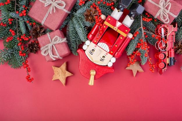 Kerst samenstelling. rode kerstversiering, spar takken met speelgoed, notenkraker, geschenkdozen op rode achtergrond. plat lag, bovenaanzicht, kopie ruimte